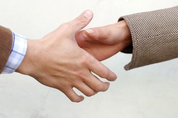 two persons about to initiate a handshake
