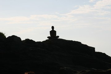 man sitting on the rocks meditating