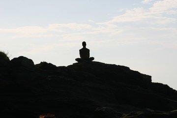 man sitting on the rocks meditating