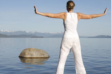woman on white spreading her arms in front of the sea