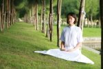 lady in white sitting on the grass and meditating