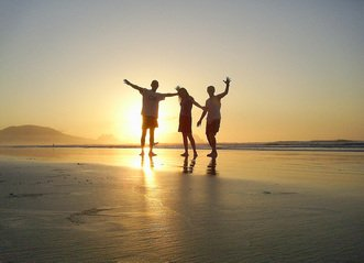 group of friends expressing happiness at the beach on sunset