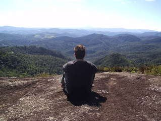 man sitting in front of mountains doing a self-talk