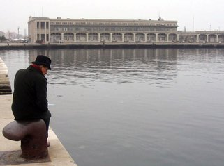man sitting in front of the lake doing a self-talk